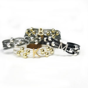 Group of four different color initial bracelets. Gray, black and white leather options.