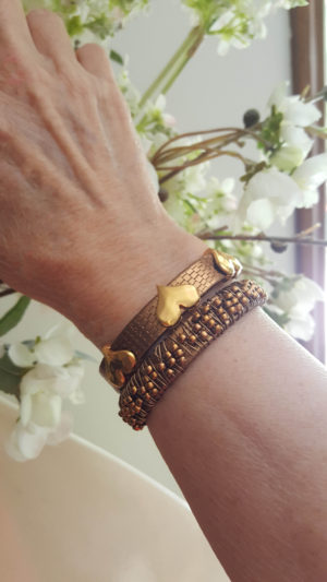 Set of bronze leather bracelets together. The bronze leather with three hearts and the brown leather wrapped with copper seed beads perfectly compliment each other.
