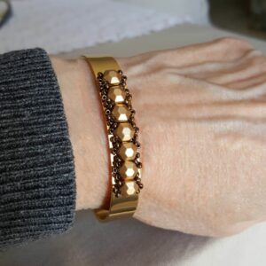 Gold Bangle Cuff on wrist is adjustable to exactly fit your wrist.