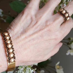 Gold bangle cuff bracelet and matching ring on hand.