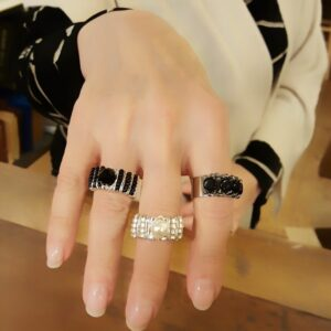 Three adjustable silver beaded rings on hand.